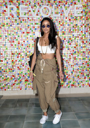 Shay Mitchell wore her khaki jumpsuit with the top half down to reveal a white sports bra during #REVOLVEfestival.