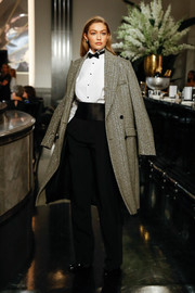 Gigi Hadid looked perfectly polished in a glittery coat layered over a white shirt and black tuxedo trousers at the Ralph Lauren Fall 2019 show.