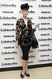 Viktoria Modesta showed her funky retro style with a belted, fitted blouse with see-through cutouts.