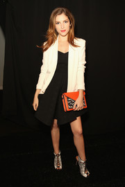 An orange envelope clutch injected a welcome pop of color to Anna Kendrick's monochrome outfit.