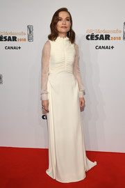 Isabelle Huppert was all about understated elegance in an ivory Dior Couture gown with a ruched bodice and sheer sleeves at the 2018 Cesar Film Awards.