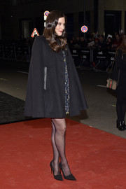 Liv Tyler arrived for the GQ Men of the Year Awards wearing a black cape over a printed mini dress.