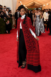 Janelle Monae made a dramatic entrance in a floor-length embroidered red and black cape by Tadashi Shoji during the Met Gala.