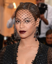 Beyonce Knowles went all out with the drama at the Met Gala, wearing dark red lipstick to complement her all-black ensemble.