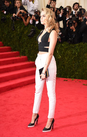 Cara Delevingne accessorized with a dark blue box clutch for an elegant finish to her look.