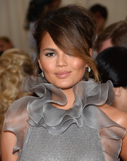 Chrissy Teigen attended the Met Gala wearing a dramatic messy updo.