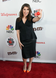 Mayim Bialik accessorized with a pair of orange PVC pumps for a pop of color to her outfit.