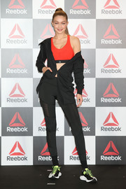 Gigi Hadid struck a pose wearing a bright red sports bra at the Reebok talk event.
