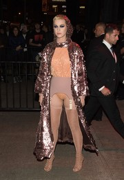 Underneath her coat, Katy Perry looked bizarre in a sparkly coral bodysuit teamed with a mauve garter belt (also by Ulyana Sergeenko).