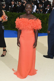 Lupita Nyong'o went the ultra-feminine route in a coral Prada off-the-shoulder gown with a mega-ruffled bustline at the 2017 Met Gala.