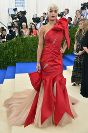 Rita Ora looked playfully glam at the 2017 Met Gala in a red and nude Marchesa one-shoulder gown that was adorned with oversized bows.