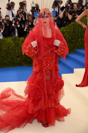Katy Perry was a standout in an embellished red coat layered over a tulle and chiffon gown, both by Maison Margiela Couture, at the 2017 Met Gala.