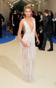 Stella Maxwell matched her dress with a white box clutch.