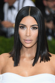 Kim Kardashian played down her kissers with nude lipstick while accentuating her eyes with some silver shadow.