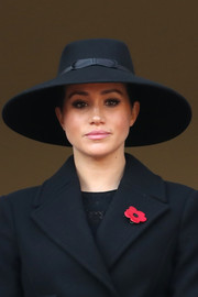 Meghan Markle accessorized with a wide-brimmed black hat at the Remembrance Sunday Cenotaph Service.