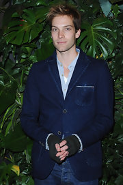 Andy wears a denim blazer with fingerless gloves for the Replay Flagship Opening.