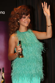 Rihanna paired her fabulously feathered at the launch of her new perfume. She punctuated her ensemble with a side-swept curly 'do.