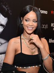 Rihanna donned layers of necklaces for the Rogue Man fragrance launch, including a gold pendant bearing her surname.