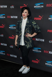 Sticking to her signature style, Demi Lovato donned a feather-print blazer and a pair of leggings for the Roc Nation pre-Grammy brunch.
