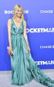 Claudia Schiffer paired her dress with a metallic silver clutch.