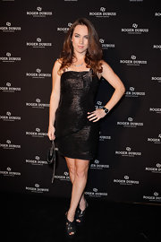 Liv Boeree paired her shiny black dress with strappy black platform sandals.