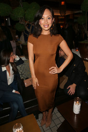 Cheryl Burke flaunted her toned physique in a body-con bronze T-shirt dress while attending the grand opening of Roku.