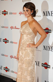 Penelope sported an elegant chignon updo with loose chin-sweeping pieces and golden highlights.