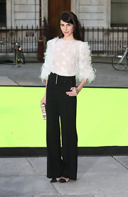 Caroline chose a pair of crisp black wide leg pants to go with her feathered top.