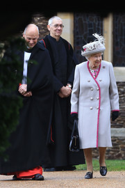 Queen Elizabeth II donned a double-breasted gray coat with fuchsia trim for Christmas Day church service.