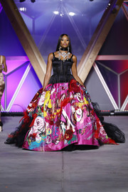 Naomi Campbell looked flamboyant in a Dolce & Gabbana corset gown with a voluminous graffiti-print skirt at the Fashion for Relief runway show.