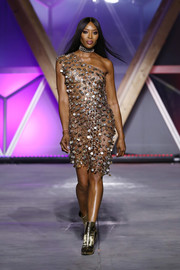 Naomi Campbell went risque in a see-through one-shoulder paillette dress at the Fashion for Relief runway show.