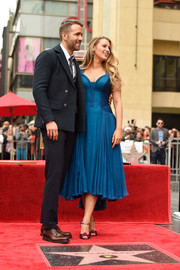 Blake Lively went for a striking color contrast, pairing her blue dress with fuchsia, gold, and purple knot-detail sandals by Christian Louboutin.