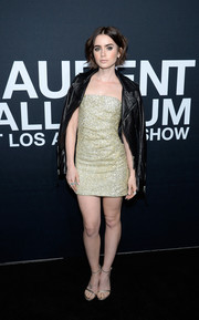 Lily Collins attended the Saint Laurent show sporting a strapless gold mini dress and black biker jacket combo.