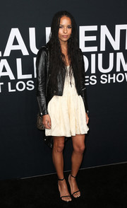Zoe Kravitz layered a black leather jacket over a cream-colored mini dress for the Saint Laurent show.