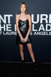 Alexa Chung showed plenty of skin in a black spaghetti-strap leather dress at the Saint Laurent show.