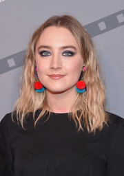 Saoirse Ronan went for playful styling with a pair of color-block pompom earrings.