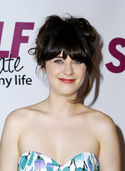 Zooey Deshcanel completed her darling look with a messy updo with wispy bangs that swept across her face.