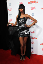 Jessica White paired her unusual cocktail dress with classically sexy strappy black sandals.