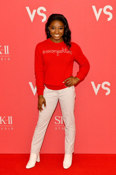 Simone Biles looked cute and comfy in her red sweater at the Beauty is #NOCOMPETITION event.