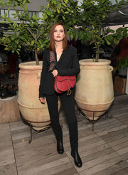 For a pop of color, Zoey Deutch accessorized with a pink leather shoulder bag by Dior.