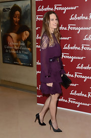 Hilary Swank attended an exhibition at the Louvre wearing a pair of black satin pumps.