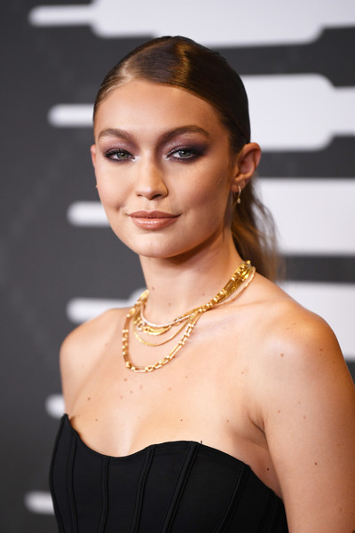 Gigi Hadid adorned her bare neckline with layers of gold necklaces.