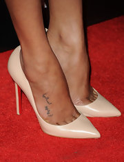 Zoe Saldana arrived at the screening of 'Colombiana' wearing beige Louboutins that showed off her discreet tattoo of an Arabic phrase.