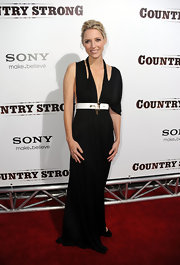 Shana wears a floor length black dress with a unique torn looking neckline.