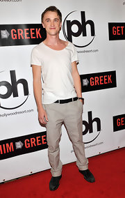 Tom Felton dressed down on the red carpet in a plain white tee worn with beige dress slacks.