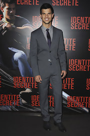 Taylor Lautner was uber dapper at the Paris premiere of 'Abduction' in a gray suit paired with a checkered shirt and a deep purple tie.