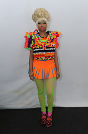 During day five of Mercedes-Benz fashion week, Nicki Minaj wore an orange, Swiss dot tennis skirt with blue lace vents.
