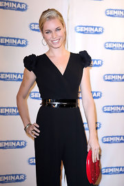 Rebecca Romijn added whimsical flare to her black jumpsuit with a sparkly red lip-shaped clutch.