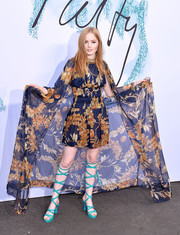 Ellie Bamber topped off her dress with a matching cape.