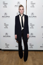Elle Fanning was sleek and stylish in a black Nomia blazer layered over a tie-neck shirt at the 'Sidney Hall' party during Sundance.